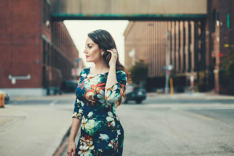 Miriam Khalil wearing a dark blue dress with a colourful floral print pattern, standing in the middle of a Toronto street and looking thoughtfully to the left. Photo by Shayne Gray.
